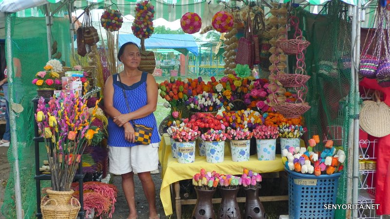 Smiling vendor selling colorful fossilized flowers. Bili na!